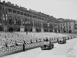 L'Alfa Romeo, con a bordo Mussolini, attraversa piazza San Carlo gremita di piccole italiane